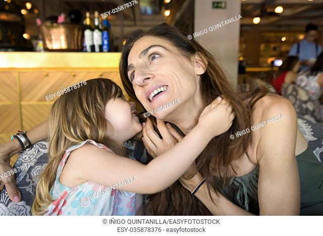 three years old blonde girl talking in the ear to woman mother sitting in restaurant
