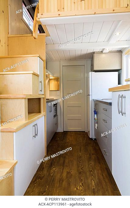 Pinewood stairs leading to the upper floor bedroom, kitchen area and bathroom doorway in the background inside a contemporary cottage style 8 x 24 foot open...