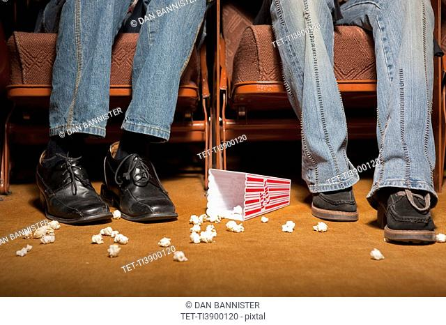 Legs and feet beside spilled popcorn in movie theatre