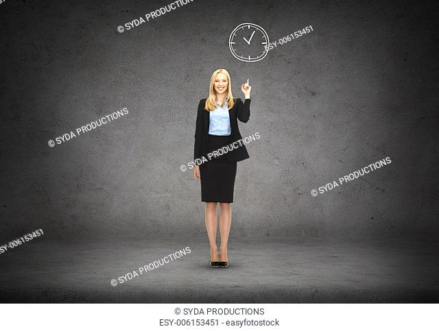business and education concept - attractive young businesswoman with her finger up and wall clock