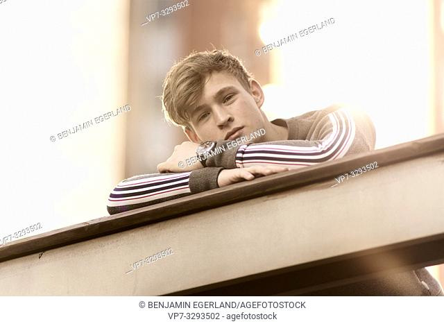 young relaxed model man leaning on railing, in Hamburg, Germany