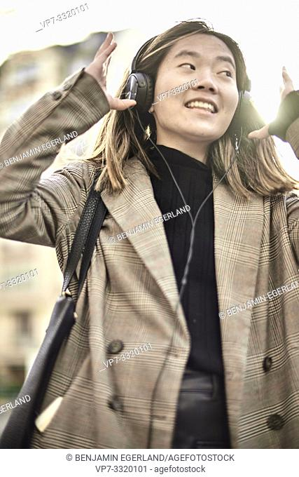 young Asian woman listening to music with headphones at street, in Paris, France