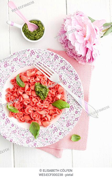 Homemade pink pasta with basil and pesto on plate