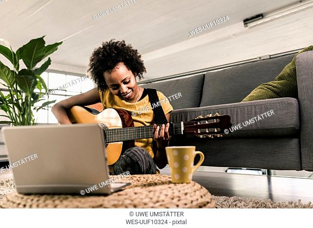 Smiling young woman at home with laptop playing guitar