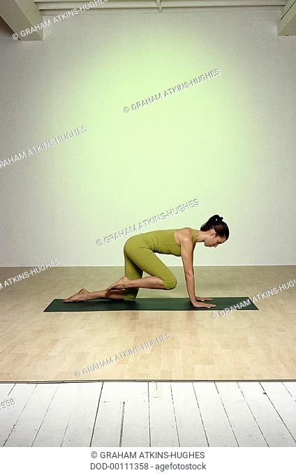 Stay Young, Knee Circles, woman moving from all-fours on green mat, profile, left knee brought forwards towards chest, abdomen drawn back, arms straight