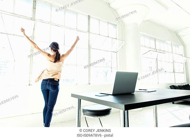 Businesswoman dancing by office window