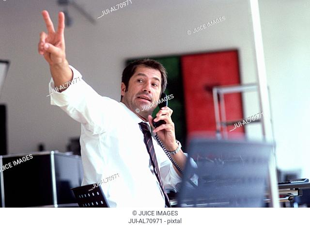 Low angle view of a young businessman signaling while talking on the phone