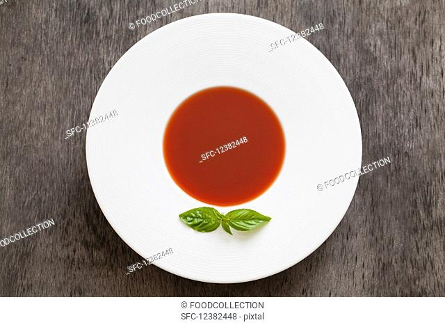 Gazpacho and tomato soup garnished with a basil leaf
