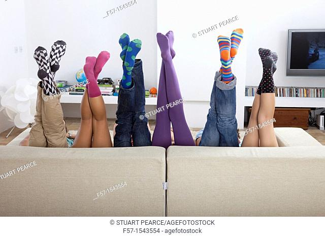 Group of friends legs sticking up over a sofa