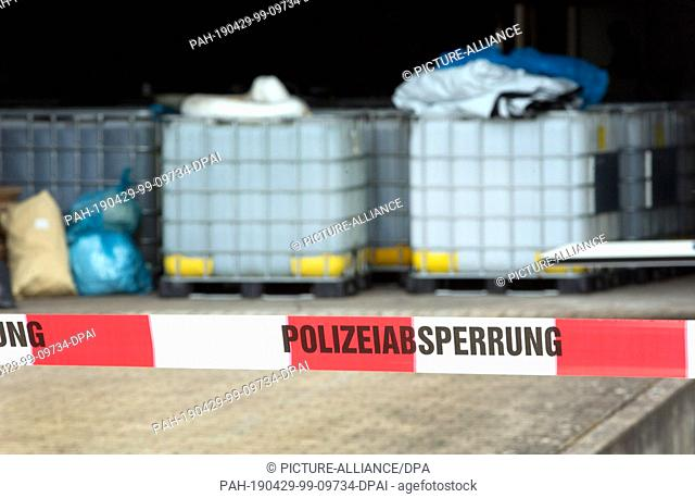 29 April 2019, North Rhine-Westphalia, Preußisch Oldendorf: Containers are standing in a warehouse that's cordoned off by the police