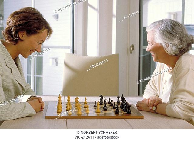 indoor, half-figure, profile, 2 women sit at a table in front of the window playing chess  - GERMANY, 11/03/2005