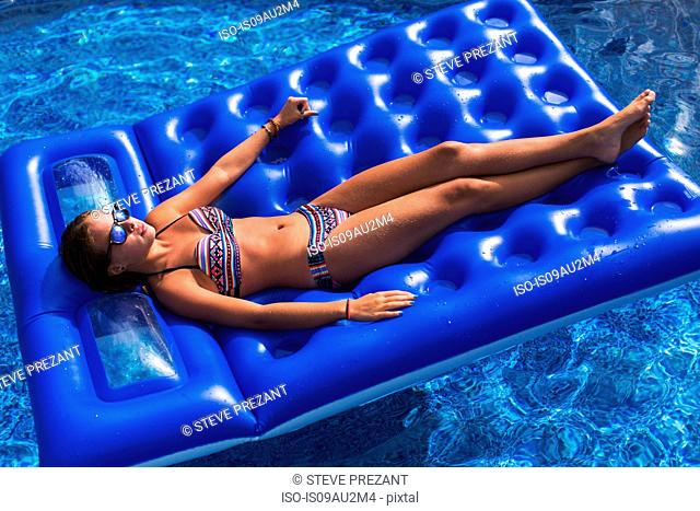 Teenager relaxing on inflatable in swimming pool