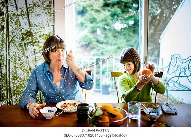 Mother and daughter (10-12 years) at dining table