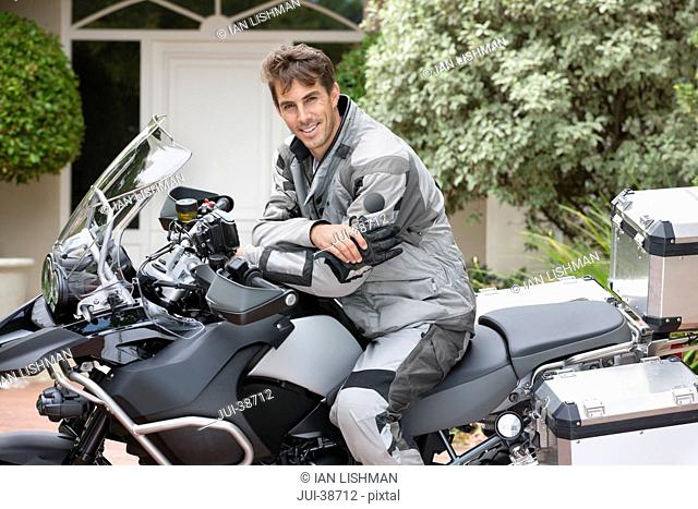 Portrait of smiling man on motorcycle in driveway
