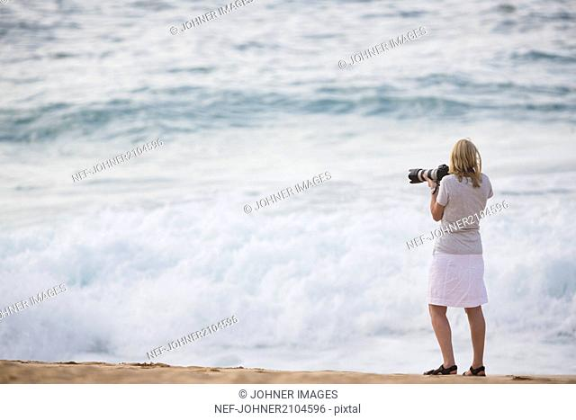 Woman taking photo on beach