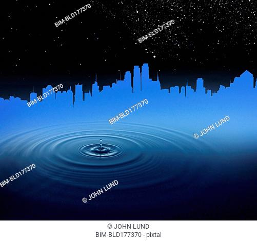 Rippling droplet in water reflecting city skyline