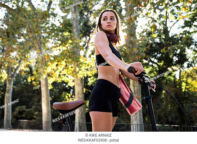Fit young woman carrying yoga mat, riding bicycle