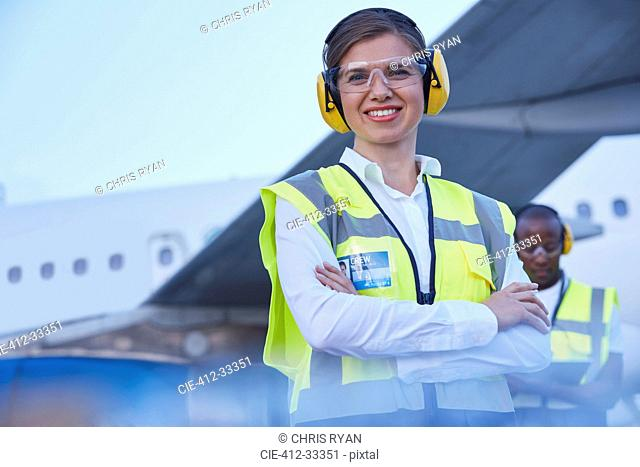 Portrait smiling female air traffic controller standing near airplane
