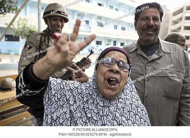 An Egyptians woman flashes the victory sign while ululating after voting on the 3rd day of the 2018 Egyptian presidential elections