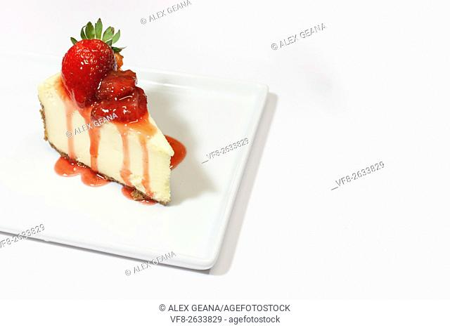 A white cheesecake with dripping strawberry sauce and a graham cracker crust, garnished with whole strawberries on a square plate