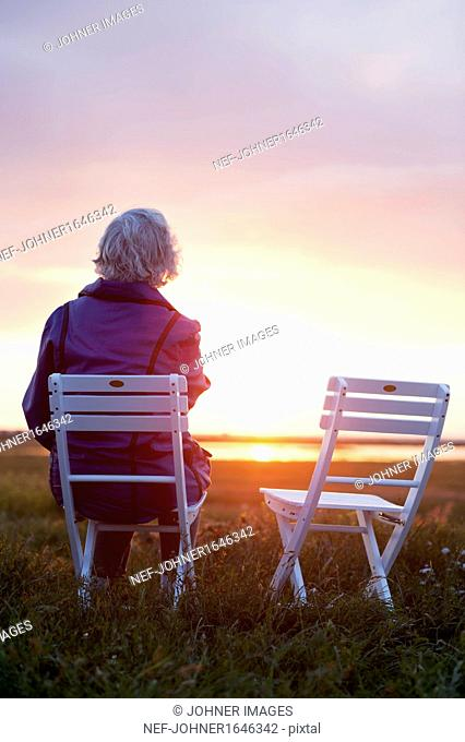 Woman sitting on wooden chair on meadow