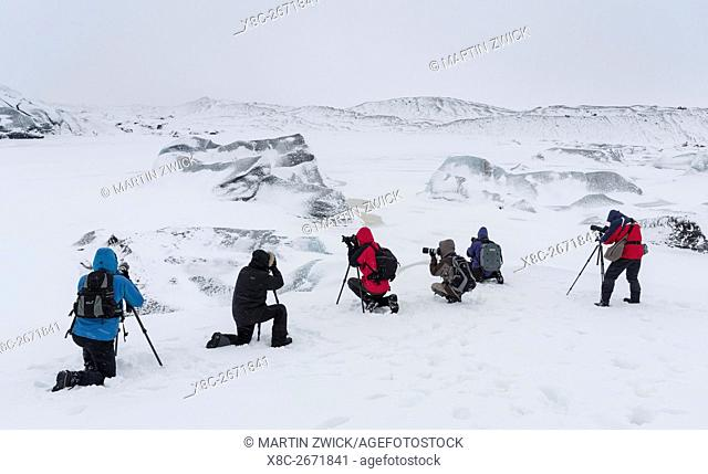 Group of photographers at glacier Svinafellsjoekul in the Vatnajoekull NP during winter. The glacier front and the frozen glacial lake
