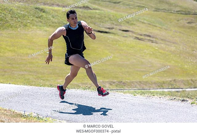 Spain, Asturias, Gijon, Athlete training outdoors, doing roadwork