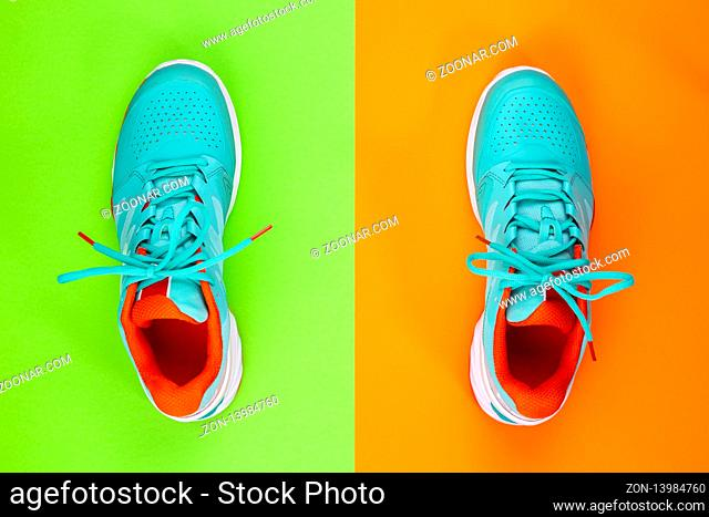 Red, cyan, white pair of new tennis shoes in studio shot over green, orange background. Directly from above