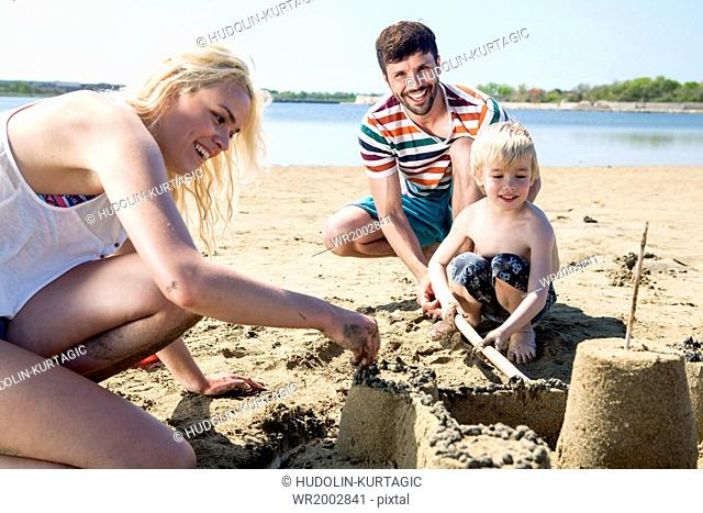 Parents and son making sandcastle on beach