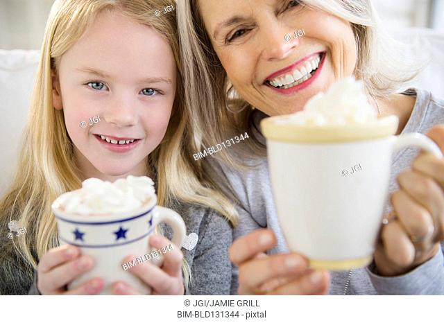Senior Caucasian woman and granddaughter drinking hot cocoa