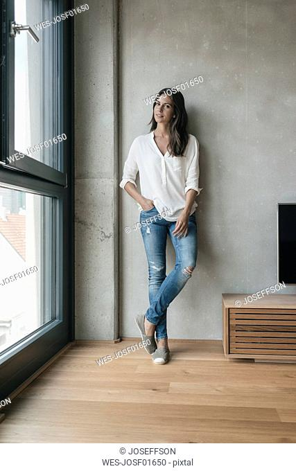 Woman standing at concrete wall
