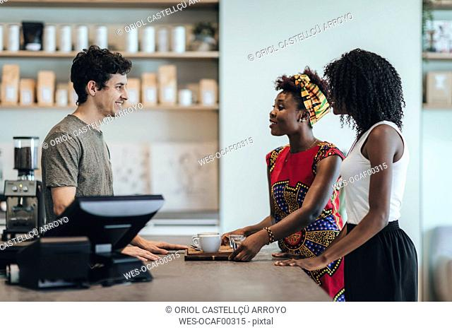 Waiter talking to customers in a coffee bar