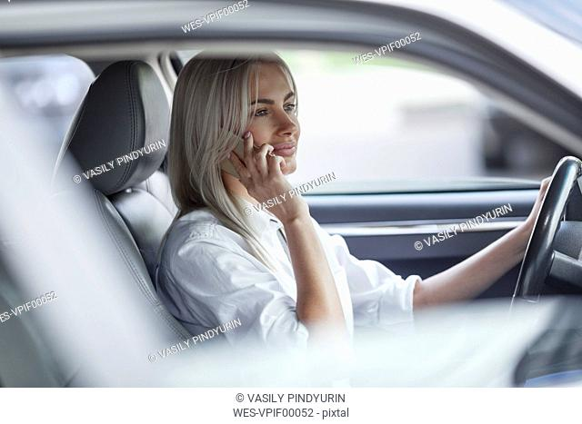 Businesswoman on cell phone driving car