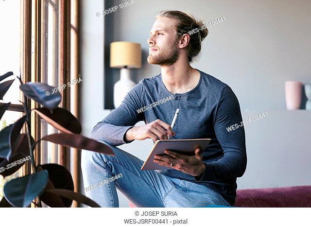 Pensive young man at home with a digital tablet looking out of a window