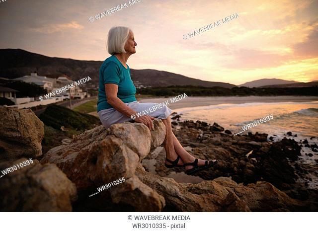 Senior woman sitting on seaside rocks