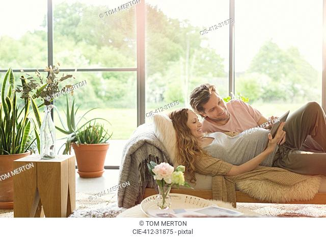 Pregnant couple laying using digital tablet in living room