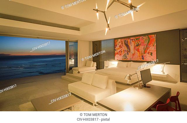 Illuminated modern, luxury home showcase interior bedroom with ocean view at dusk