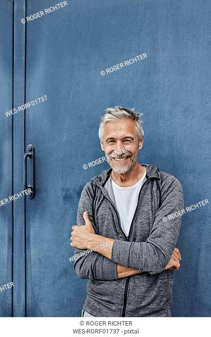 Portrait of laughing mature man standing in front of gym