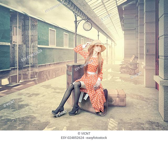 The girl sitting on the suitcase waiting at the retro railway station. Vintage color cards style