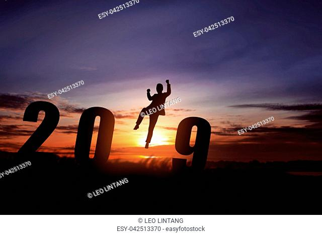 Silhouette of businessman jump to celebrate 2019 with sunset background. Happy New Year 2019