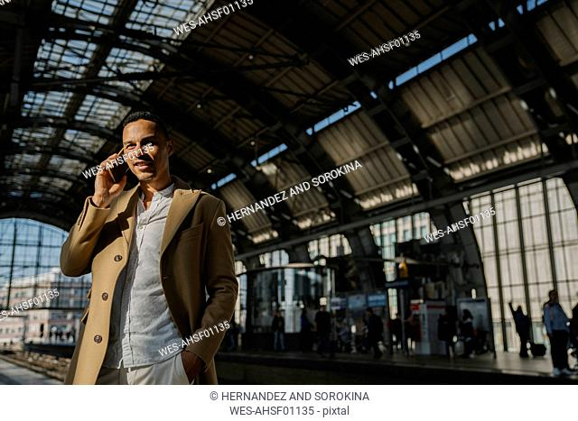 Portrait of businessman on the phone standing at train station Alexanderplatz, Berlin, Germany