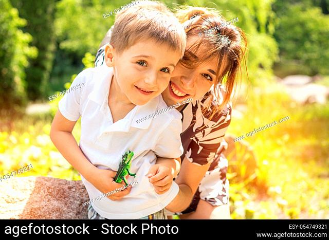 Happy little boy playing with his mother in the city park on a summer sunny day. Mother and son in the park near pond