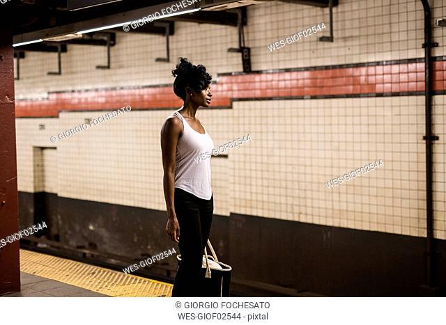 USA, New York City, Manhattan, woman with shopping bag waiting at subway station platform