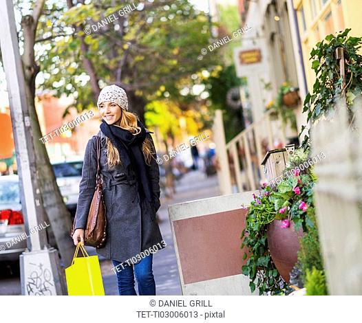 Portrait of blond woman walking on sidewalk