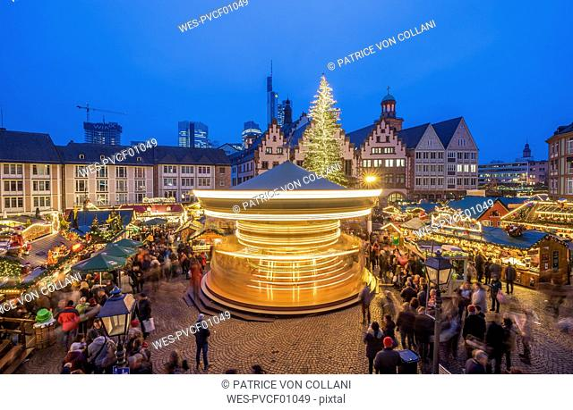 Germany, Frankfurt, rotating carousel on Christmas market at Roemerberg in the evening