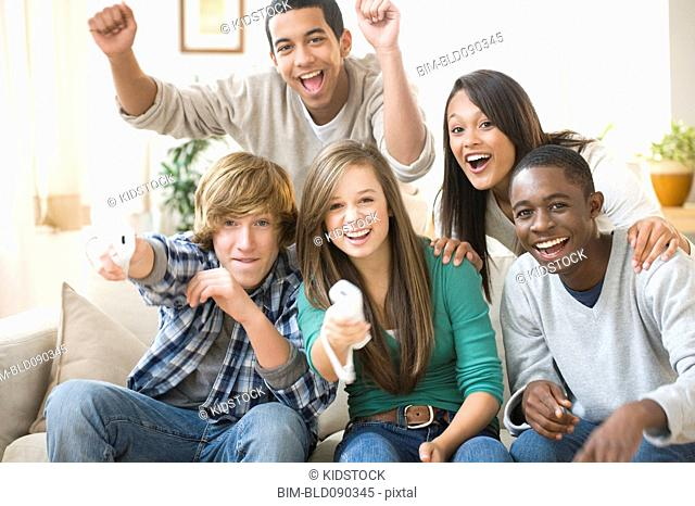 Teenagers playing video game together