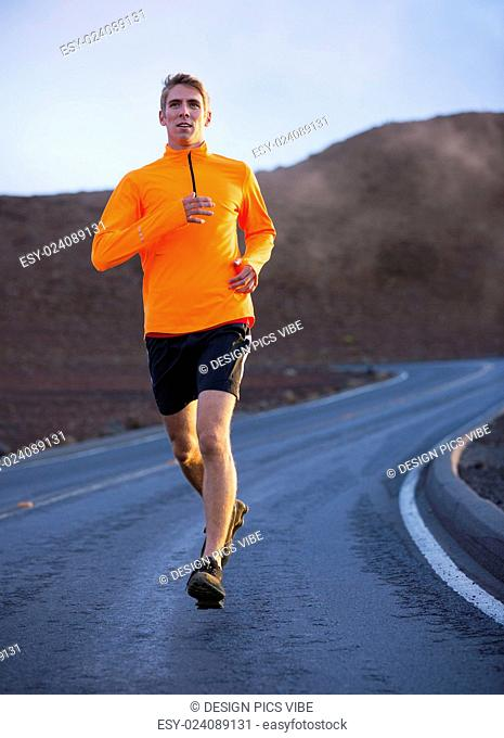 Athletic man jogging outside, training outdoors. Running on road at sunset