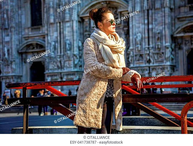 Rediscovering things everybody love in Milan. young traveller woman in fur coat and sunglasses in the front of Cathedral in Milan