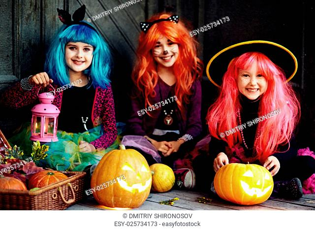 Group of girls looking at camera on Halloween night surrounded by jack-o-lanterns