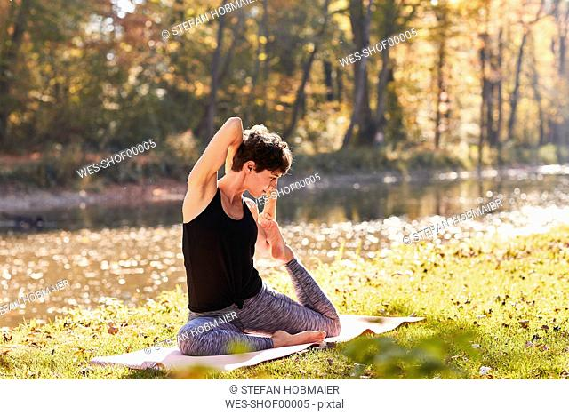 Mid adult woman in forest practicing yoga